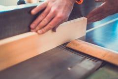 Le charpentier s'est engagé en traitant le bois à la scierie Humain masculin rotatoire Pers de la poussière DIY de mouvement de f Image libre de droits