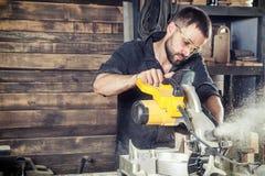 Le charpentier scie une scie circulaire moderne photographie stock libre de droits