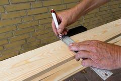 Le charpentier tenant une équerre et trace une ligne photo stock