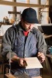 Le charpentier tient un meuble en bois photos stock