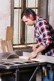Le charpentier travaillant à un bourdonnement électrique a vu couper quelques conseils Images libres de droits