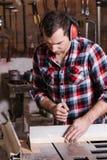 Le charpentier travaillant à un bourdonnement électrique a vu couper quelques conseils Photographie stock libre de droits