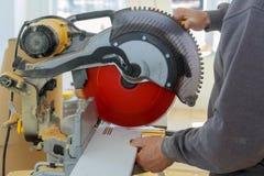 Le charpentier travaillant utilisant la rotation circulaire de scie a vu la plinthe en bois de coupe photo libre de droits