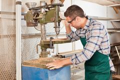 Le charpentier travaille ? une perceuse photo stock