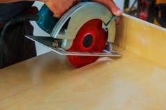 le charpentier utilise une scie circulaire pour couper le bois sur la zone de manoeuvre Photographie stock