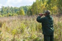 Le chasseur appelle un orignal pendant la chasse d'ornière photographie stock libre de droits