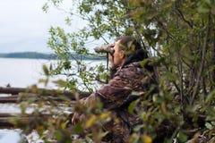 Le chasseur regarde par les jumelles la rivière Photographie stock