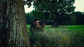 Le chasseur s'asseyant sous un arbre et visent la proie clips vidéos