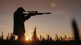Le chasseur vise d'un fusil avec un appareil optique de visée Il se tient dans un endroit pittoresque au coucher du soleil Photographie stock
