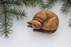 Le chat fait main en bois de jouet avec des branches d'arbre de sapin sur la neige blanche Fond de Noël photo libre de droits