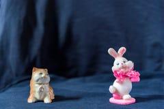 Le chat menteur de sculpture avec un collier avec un diamant regarde le lapin de rose de jour de valentines sur le fond noir Photos stock