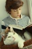 Le chat s'étendent dans le lit d'animal familier avec le livre de lecture de garçon Images stock