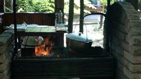 Le chaudron dans quelle soupe ou toute autre nourriture est préparé accroche le balancement au-dessus du bois de chauffage et des clips vidéos