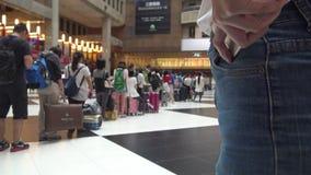 le cheack asiatique de la femme 4K le téléphone, foule des voyageuses de personnes achètent le billet de train banque de vidéos