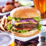 Le cheeseburger avec de la bière et les pommes frites se ferment  Photographie stock libre de droits