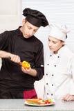Le chef aîné enseigne le jeune chef à décorer le fruit Photo stock