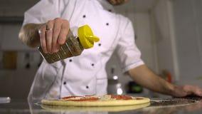 Le chef arrose des épices sur la pizza de finition dans la cuisine banque de vidéos