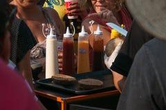 Le chef avec le couteau, coupant le pain d'hamburger pour la foule En particulier les sauces basées sur la mayonnaise, rattrapent images stock