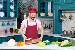 Le chef barbu dans le chapeau tient couper le conseil en bois dans des mains Photos stock