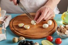 Le chef coupe l'oeuf de caille bouilli sur la planche à découper en bois sur la table de cuisine bleue image stock