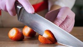Le chef coupe la fraise sur des tranches dans les gants en caoutchouc sur la table en bois image libre de droits