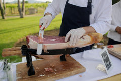 Le chef coupe le jambon de mains Image stock