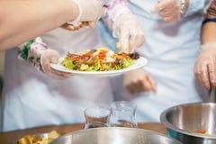 Le chef décore la salade avec des verts photos libres de droits