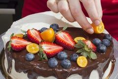 Le chef décore le gâteau de baie avec le kumquat Images stock