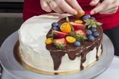 Le chef décore le gâteau de baie avec le kumquat Photos stock