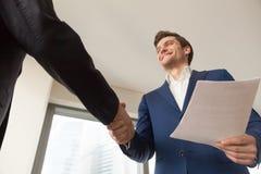 Le chef d'entreprise de sourire souhaitant la bienvenue au client dans le bureau Photographie stock