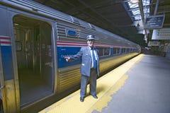 Le chef d'orchestre à la plate-forme de train d'Amtrak annonce tous à bord à la station de train de Côte Est sur le chemin à New  Photographie stock libre de droits