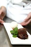 Le chef dans le restaurant offre le dessert Image libre de droits