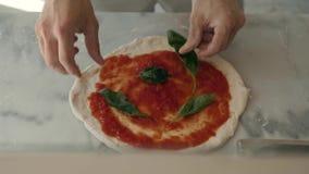 Le chef dans le restaurant prépare une pizza et la décore avec du mozzarella et le basilic de tomate