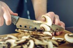 Le chef dans le tablier noir coupe des champignons avec un couteau Concept des produits qui respecte l'environnement pour la cuis photos stock