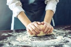 Le chef dans le tablier noir fait la pâte de pizza avec vos mains sur la table Photos stock