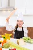 Le chef de fille d'enfant sur le geste drôle de partie supérieure du comptoir avec le rouleau malaxent Photo stock