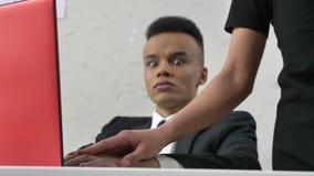 Le chef de jeune femme touche doucement la main de son employé gêné africain, flirtant, fps du concept 50 de harcèlement banque de vidéos