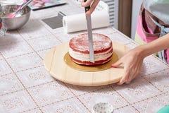 Le chef de pâtisserie à la maison enseigne à alignement le gâteau Photo libre de droits