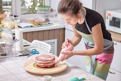 Le chef de pâtisserie à la maison enseigne comment niveler un gâteau avec de la crème Photo libre de droits