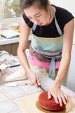 Le chef de pâtisserie à la maison enseigne faire cuire le gâteau rouge Photo stock