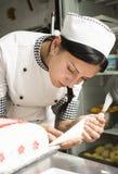 Le chef de pâtisserie décore un gâteau photos libres de droits