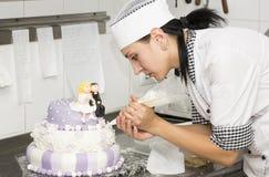 Le chef de pâtisserie décore un gâteau Photos stock