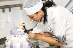 Le chef de pâtisserie décore un gâteau Photo stock