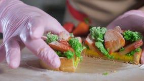 Le chef de pâtisserie dans les gants en caoutchouc montre le remplissage de la coupure en mini gâteau de demi fraise clips vidéos