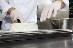 Le chef de pâtisserie de mains prépare un gâteau, glaçage blanc se renversant de couverture, travaillant à un dessus de travail d photos stock