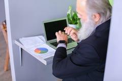 Le chef de tête de vieil homme finit le jour ouvrable, séance à l'ordinateur portable à Photo libre de droits