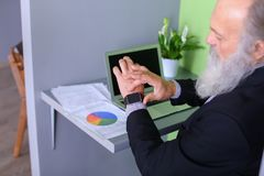 Le chef de tête de vieil homme finit le jour ouvrable, séance à l'ordinateur portable à Photo stock