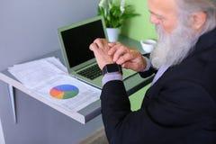 Le chef de tête de vieil homme finit le jour ouvrable, séance à l'ordinateur portable à Images libres de droits