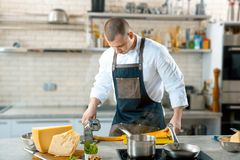Le chef fait la pâte mince avec la machine spéciale, image modifiée la tonalité image stock