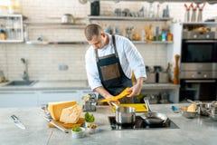Le chef fait la pâte mince avec la machine spéciale, image modifiée la tonalité images libres de droits